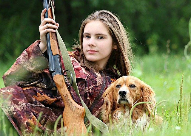 girl with a hunting rifle and dog